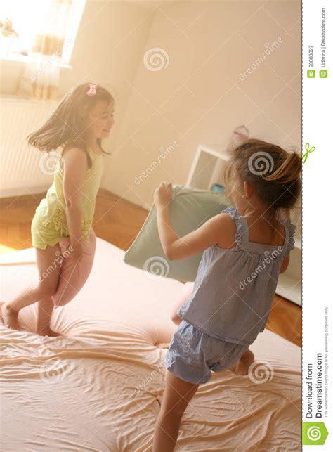 ragazze sul letto le ragazze stanno divertendo sul letto immagine stock