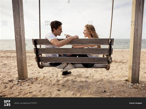 2 couples swinging couple sitting on a wooden swing on a beach stock photo