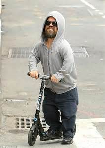 peter dinklage dons grey hoodie while riding his scooter