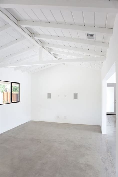 polished concrete, white walls, exposed beams, black