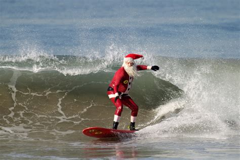 santa on surfboard surfing santa returns to the hermosa pier