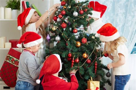 group of adorable kids in santa caps decorating xmas tree