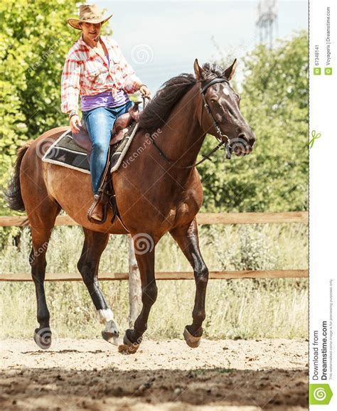 training active ranch western cowgirl woman riding horse sport activity stock