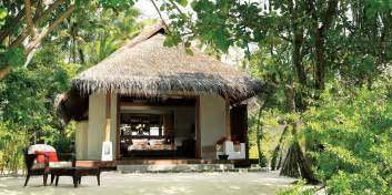 Bungalow hotel in males with thatched roof white exterior design