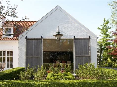 fashioned barn barn sliders on white brick dining room addition with