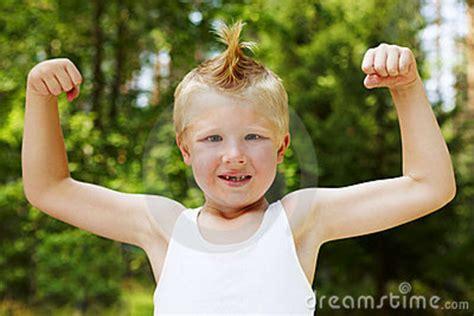 little boy flexing bicep portrait of cute little boy flexing his muscles royalty