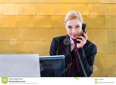 Hotel Front Desk Phone Number by Hotel Receptionist With Phone On Front Desk Stock Photo