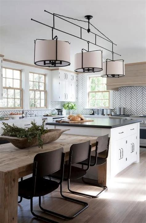 a three light drum pendant hangs over a white kitchen