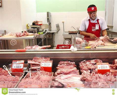meat section in grocery store a butcher at a meat section of a grocery store editorial