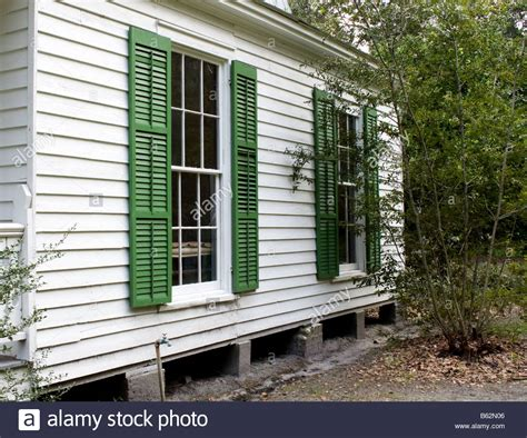 shutters on side of house side of a white house with green shutters on the windows in mandarin stock photo