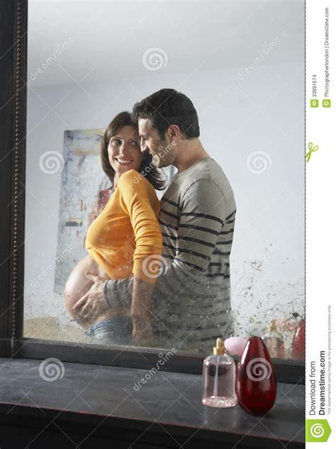 man and woman in the bedroom reflection of man embracing pregnant woman stock images