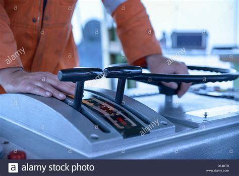 tug boat controls worker manning tugboat controls stock photo royalty free