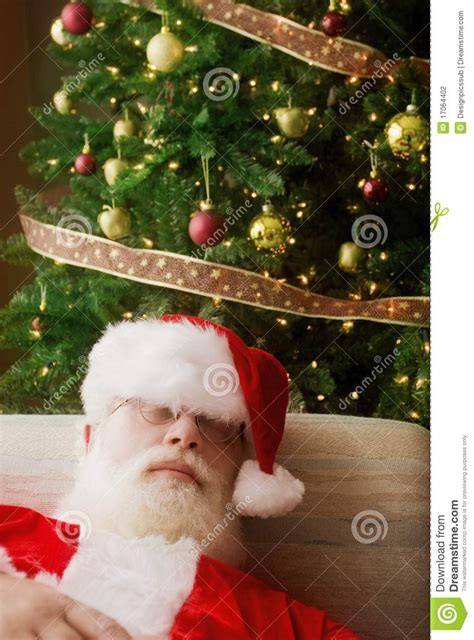 santa claus asleep in front of christmas tree stock