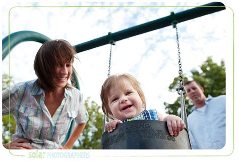 mom swings baby around fun family pictures in loose park kansas city