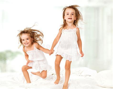 giochi sul letto famiglia felice i bambini gemellano le sorelle che saltano