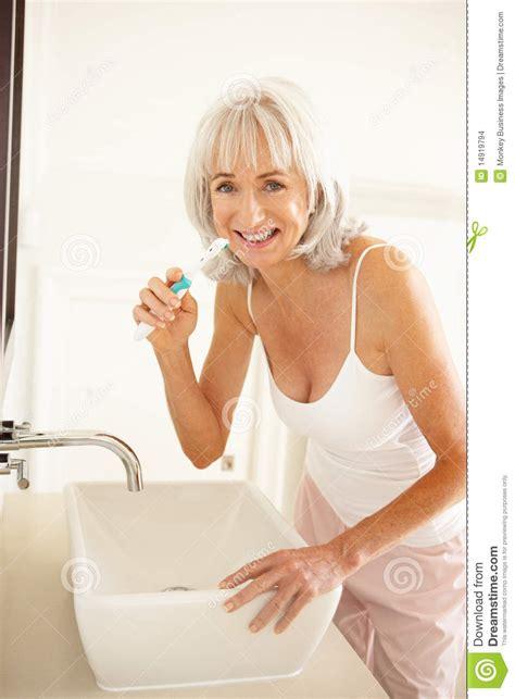 mature bathtub senior woman brushing teeth in bathroom stock images