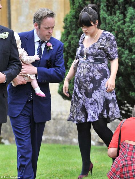 Lily Allen displays her growing baby bump in purple frock