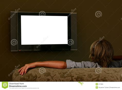couch tu boy sitting on couch watching widescreen television stock