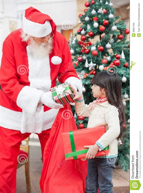 santa claus giving gifts to girl stock photo image 36831194