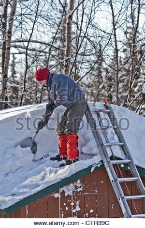anchorage roof shoveling a standing by shed with shovel stock photo royalty