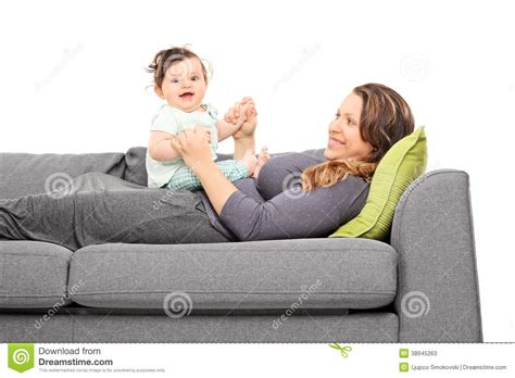 lying on a sofa woman lying on sofa and looking at her daughter stock