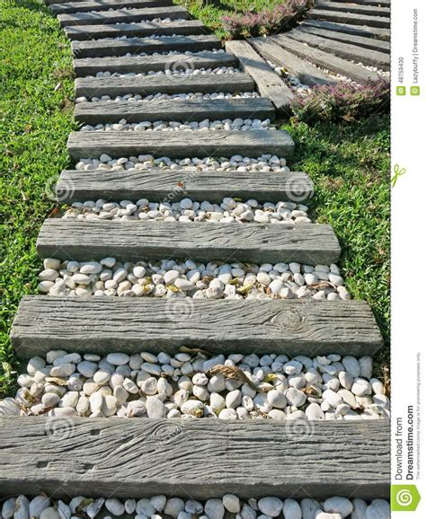 wood and small white rocks pathway on grass in the garden