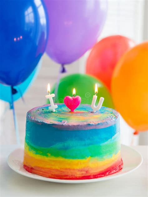 rainbow cake and cupcakes decorated with birthday candles rainbow cake and cupcakes balloons on the background stock image image of slice colorful