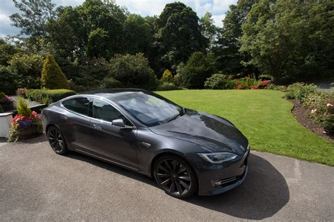 tesla outside driving the tesla model s through the countryside watch