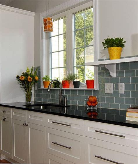 white kitchen black counter black counter top with aqua green backsplash tiles and