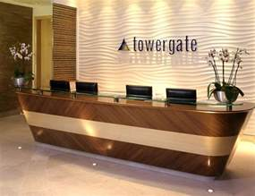 Hotel Reception Desk Furniture Textured Light Colored Wall With Recessed Lighting Wood Paneled Desk W White Marble Top