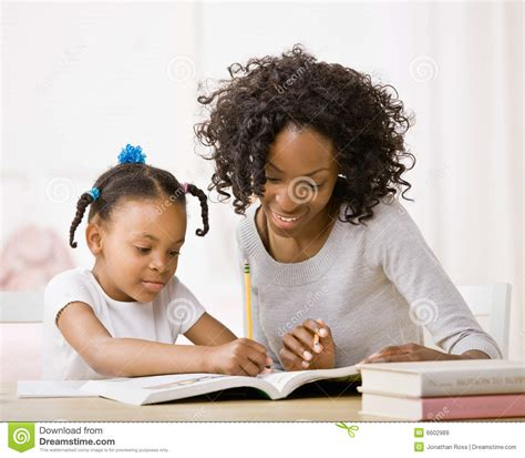 Mother Helping daughter Do Homework In Workbook Royalty