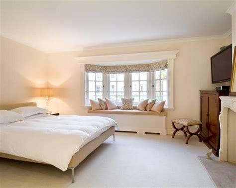 bay window bedroom furniture photo of neutral beige white dark wood bedroom with bay
