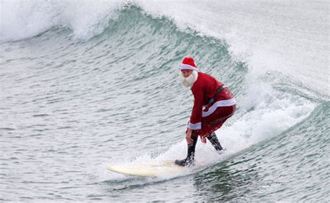 santa on surfboard santa claus surfing golfing and biking popsugar fitness