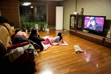 family watching tv with popcorn in living room stock photo asian family watching tv together in living room this is