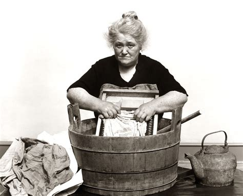 washing clothes in bathtub 1930s 1940s senior woman washing clothes in old fashioned