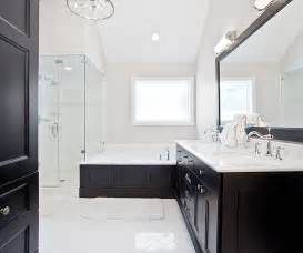 black and white bathroom features black framed mirror