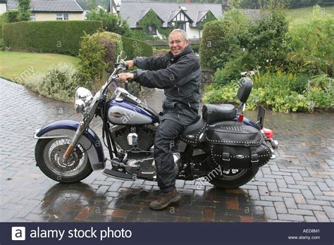 buying a house at 60 years old 60 year old man with harley davidson motorbike outside his house stock photo royalty