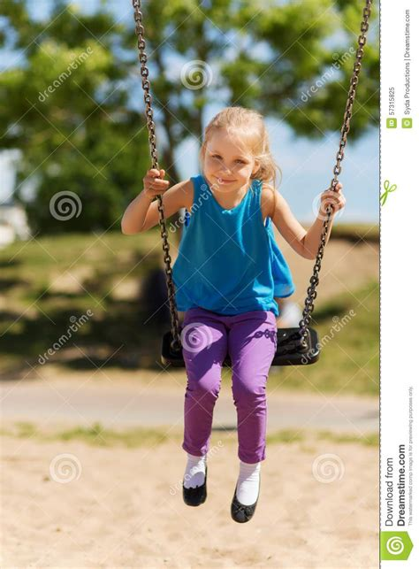 little girl swinging happy little girl swinging on swing at playground stock