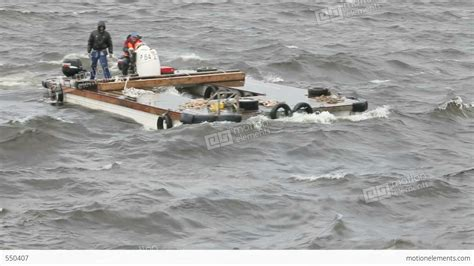 two men on a motor catamaran sailing in a storm stock - Catamaran Storm Video