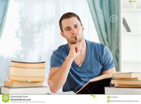 Student Sitting At His Desk Doing His Homework Stock Student Sitting At Desk