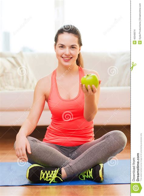 smiling with green apple at home stock image