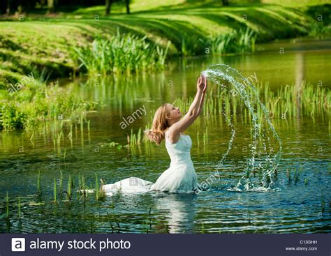 woman lady walking into lake water up to her waist in long
