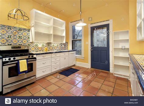 Kitchen in suburban home with terra cotta floor tile and