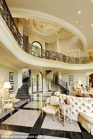 Grandiose the hallway boasts sweeping staircases and ornate iron