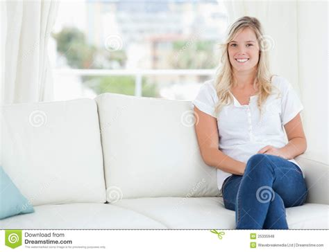 sitting on the couch a woman sitting on the couch smiling royalty free stock