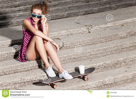 youth spread beautiful lady in jeans shorts with skateboard at stone
