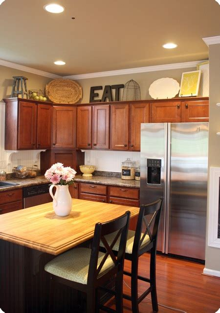 Decorating Ideas For Above Kitchen Cabinets How To Decorate Above Kitchen Cabinets From Thrifty Decor