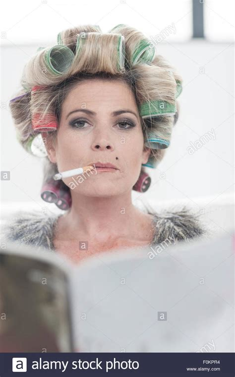 smoking in curlers portrait of woman with hair curlers and magazine smoking a