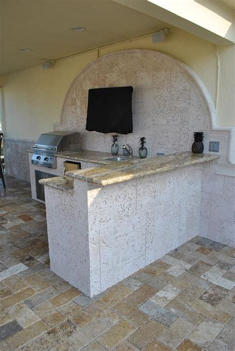 bar top overhang outdoor kitchen with coral stone walls over granite bar