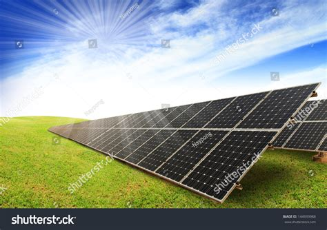 solar panels on green grass with blue sky stock photo